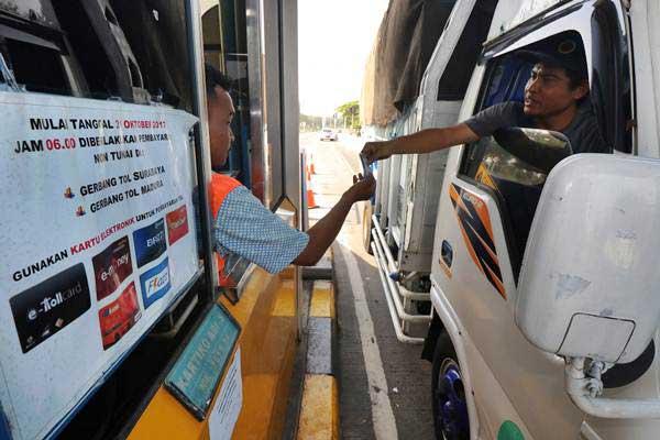 Pengendara truk membeli kartu elektronik tol (E-Toll) di loket pintu masuk Jembatan Suramadu, Surabaya, Jawa Timur, Selasa (31/10). Terhitung mulai Selasa (31/10). - ANTARA/Didik Suhartono