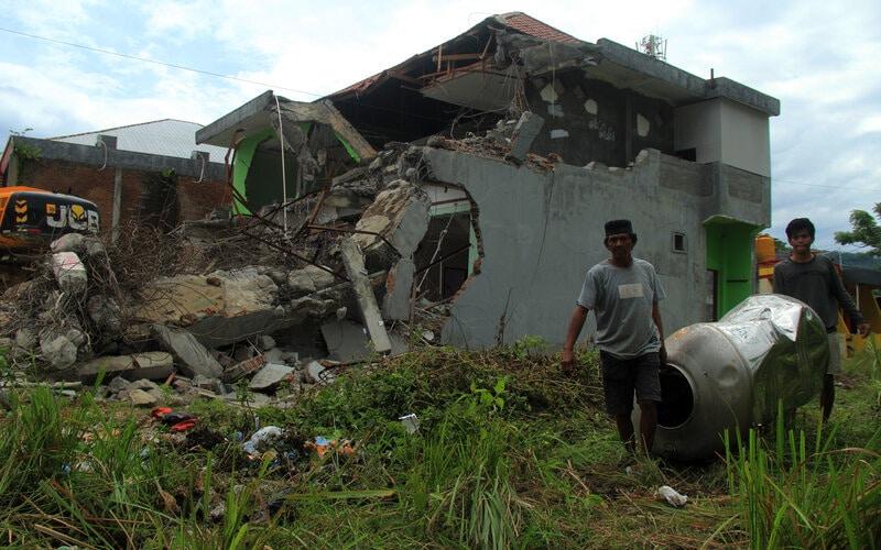 Warga mengambil barang dari sisa reruntuhan bangunan di Mamuju Sulawesi Barat, Jumat (29/1/2021). Memasuki dua pekan pascagempa bumi BNPB merilis jumlah kerusakan rumah sebanyak 7.863 unit, Mamuju 3.741 dan Majene 4.122 unit. - Antara/Akbar Tado.