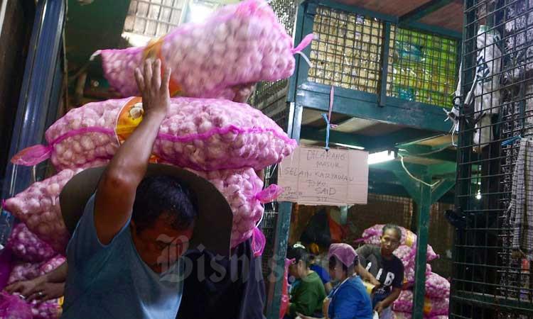 Pedagang bawang putih beraktifitas di salah satu pasar di Jakarta, Selasa (3/3/2020). Bisnis - Abdurachman