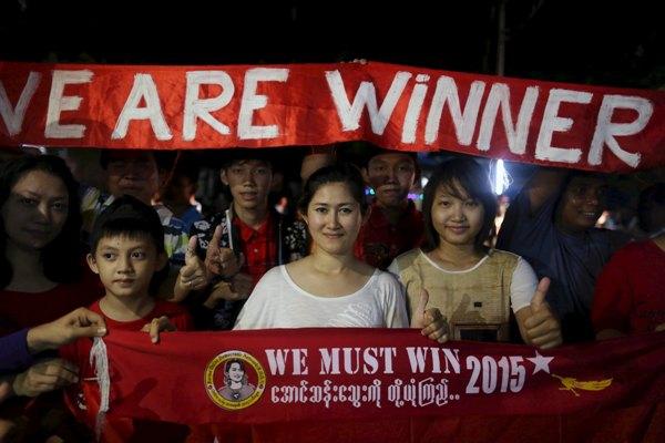 Ilustrasi - Pendukung Suu Kyi membawa spanduk saat berkumpul di halaman markas NLD di Yangon untuk menyaksikan hasil pemungutan suara yang ditayangkan televisi (8/11/2015). - Reuters/Soe Zeya Tun