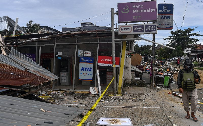 Warga melintas di dekat anjungan tunai mandiri yang rusak akibat gempa bumi magnitudo 6,2 di Mamuju, Sulawesi Barat, Sabtu (16/1/2021). - Antara