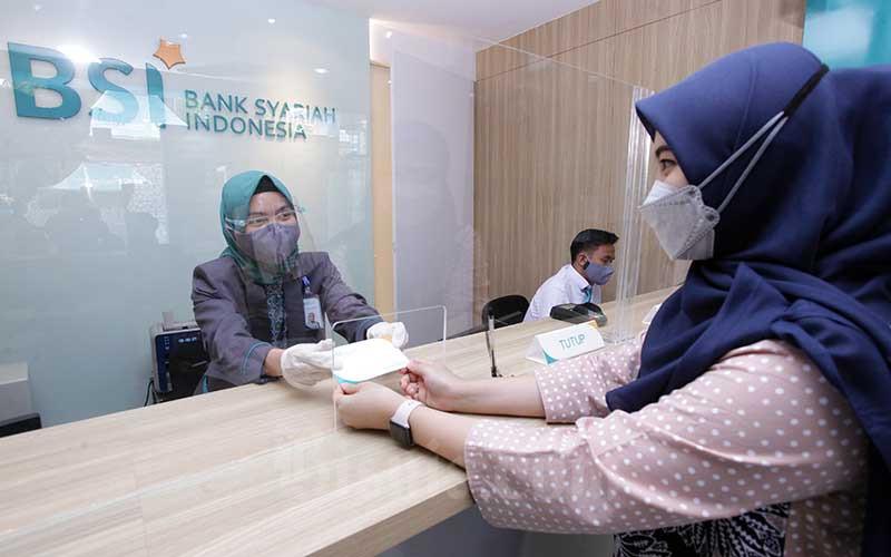Karyawan melanyani nasabah yang melakukan transaksi di PT Bank Syariah Indonesia KC Jakarta Barat, Kebon Jeruk, Jakarta, Senin (1/2 - 2021). Bisnis