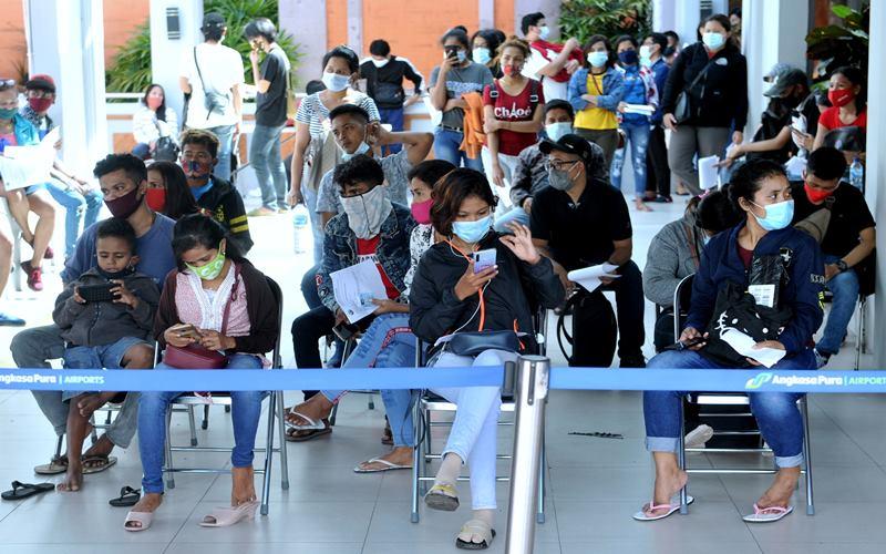 Warga antre saat akan melakukan tes cepat (rapid test) Covid-19, di area Terminal Domestik Bandara Internasional I Gusti Ngurah Rai, Badung, Bali, Jumat (18/12/2020). - Antara/Fikri Yusuf.