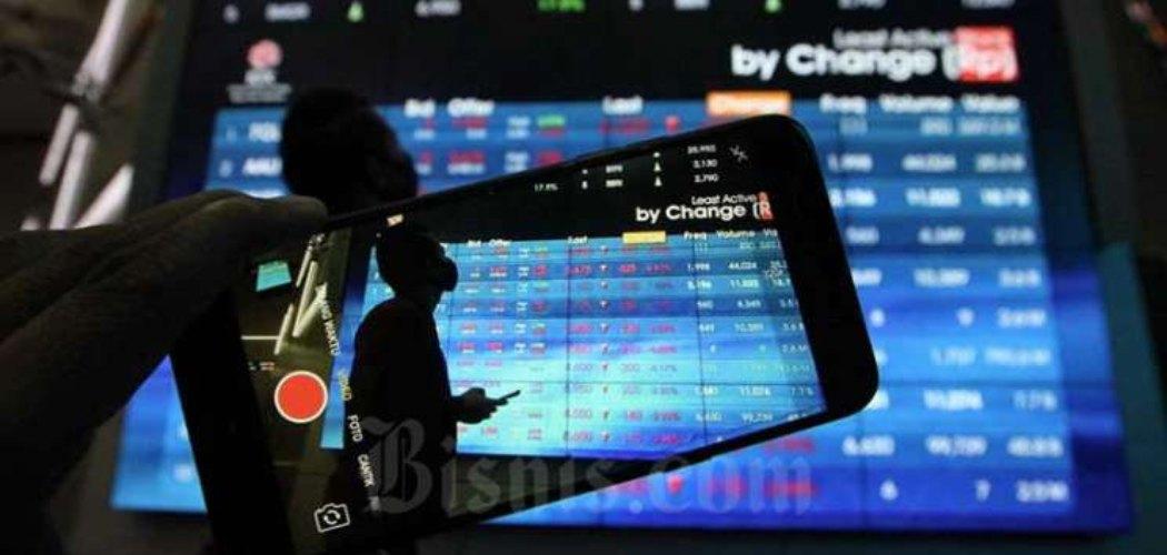 Pengunjung menggunakan smarphone didekat papan elektronik yang menampilkan perdagangan harga saham di Jakarta, Rabu (22/4 - 2020). Bisnis / Dedi Gunawan