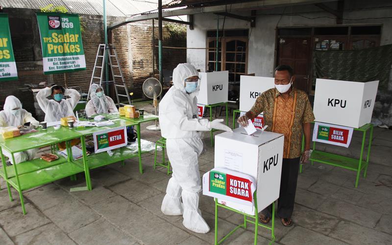 Petugas KPPS mengenakan pakaian hazmat dan Alat Perlindungan Diri (APD) di Tempat Pemungutan Suara (TPS) 039 pada Pilkada Kota Solo 2020 di Dukuhan, Nayu, Banjarsari, Solo, Jawa Tengah, Rabu (9/12/2020). TPS dengan tema Sadar Prokes (Protokol Kesehatan) tersebut dibuat untuk meningkatkan partisipasi pemilih dan mengantisipasi penyebaran COVID-19 pada Pilkada Kota Solo 2020. - Antara