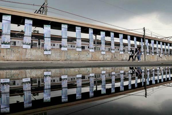 Warga melintas di dekat spanduk iklan rumah susun dengan konsep transit oriented development (TOD) di Stasiun Pondok Cina, Depok, Jawa Barat, Senin (2/10)./Bisnis - Nurul Hidayat