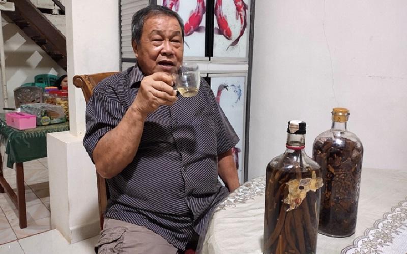 Petrus Mait, seorang warga masyarakat di Tomohon, Sulawesi Utara, sedang menikmati minuman keras tradisional cap tikus yang telah diracik dengan beberapa rempah tambahan untuk memperkuat cita rasanya, Sabtu (2/1/2021). - Bisnis/Emanuel B. Caesario.