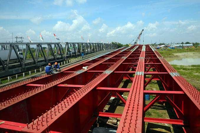 Pekerja menyelesaikan pembangunan Jembatan Kolonel Sunandar atau Tanggulangin III di jalan jalur Pantura Kudus-Demak, Jawa Tengah, Selasa (2/4/2019). - ANTARA/Yusuf Nugroho