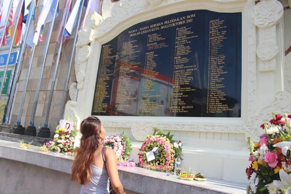 Seorang warga berdoa dan menaruh karangan bunga di Monumen Bom Bali. - Bisnis