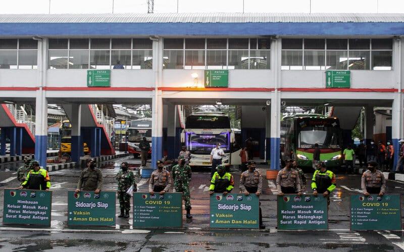 Petugas gabungan membawa poster himbauan penerapan 5M protokol kesehatan di Terminaal Purabaya, Bungurasih, Sidoarjo, Jawa Timur, Kamis (4/2/2021). Sosialisasikan penerapan 5M protokol kesehatan di kawasan terminal dalam pelaksanaan Pembatasan Kegiatan Masyarakat (PPKM) tersebut dilaksanakan Polda Jatim dan Pangdam V Brawijaya bersama Forkopimda Sidoarjo dengan membagikan masker dan sembako kepada penumpang dan kru bus. - Antara/Umarul Faruq.