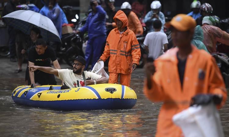 Warga menaiki perahu karet saat melintasi banjir di kawasan Kemang Raya, Jakarta, Selasa (25/2/2020). Tingginya intensitas hujan mengakibatkan sejumlah wilayah di ibu kota terendam banjir. - ANTARA/Wahyu Putro A