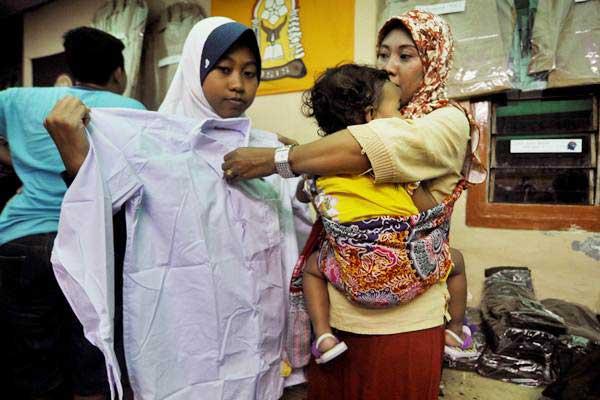 Seorang ibu mengukur seragam sekolah untuk anaknya di Pasar Induk Rau, Serang, Banten, Minggu (9/7). - ANTARA/Asep Fathulrahman