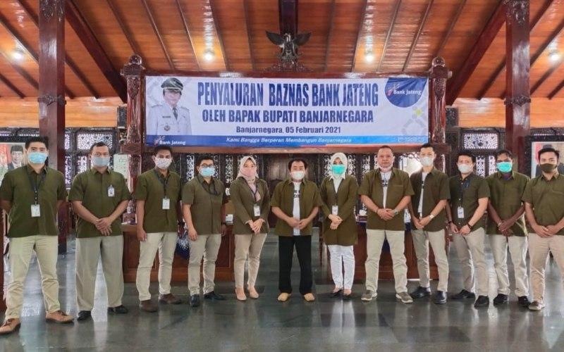Bupati Banjarnegara Budhi Sarwono berfoto bersama tim dari Bank Jateng Cabang Banjarnegara seusai melaksanakan pembagian zakat untuk 100 orang di Kabupaten Banjarnegara.