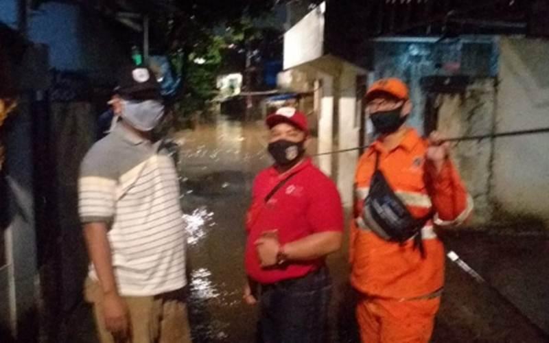 Petugas Satgas Banjir Kelurahan Pejaten Timur, Kota Jakarta Selatan bersiaga memantau pergerakan air akibat luapan Sungai Ciliwung, Minggu (7/2/2021)./Antara - HO/Kelurahan Pejaten Timur