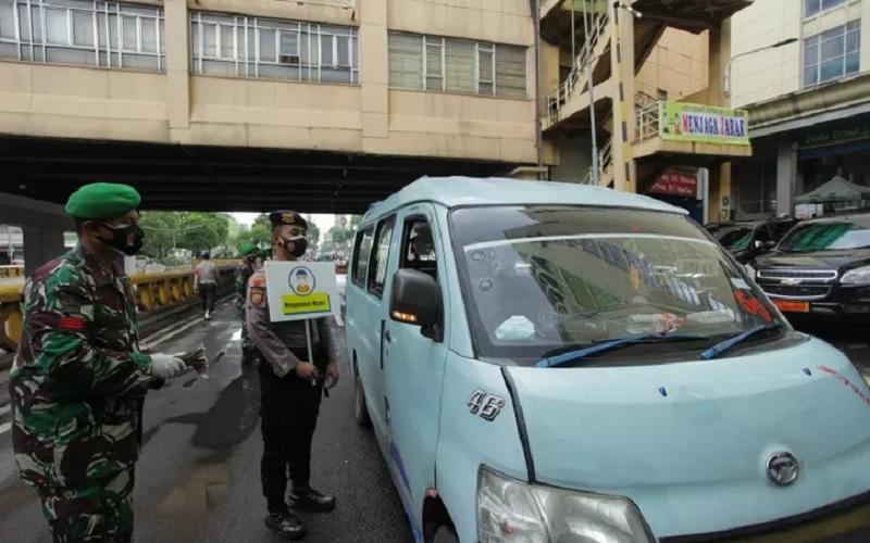 Anggota Polri melakukan imbauan untuk menggunakan masker pada warga yang beraktivitas di Jalan Medan Merdeka Barat, Jakarta, Minggu (6/9/2020). - Antara\r\n\r\n