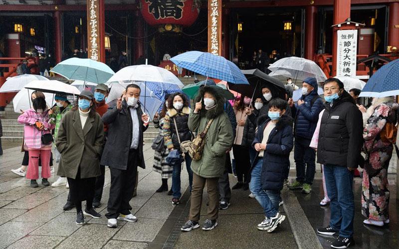 Turis mengenakan masker berkumpul di depan kuil Sensoji di distrik Asakusa, Tokyo. Pemerintah Jepang sedang meninjau kembali status darurat, sebelum mencabut status darurat tersebut/Bloomberg - Akio Kon
