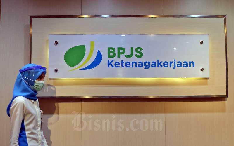 Pegawai melintasi logo BPJS Ketenagakerjaan di Kantor Cabang BP Jamsostek di Menara Jamsostek, Jakarta, Jumat (10/7/2020). Bisnis - Eusebio Chrysnamurti