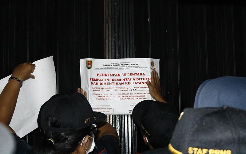Petugas Satpol PP Kota Semarang menutup tempat usaha yang melanggar ketentuan PPKM, Rabu (13/1/2021). JIBI - Bisnis/ Muhammad Faisal Nur Ikhsan