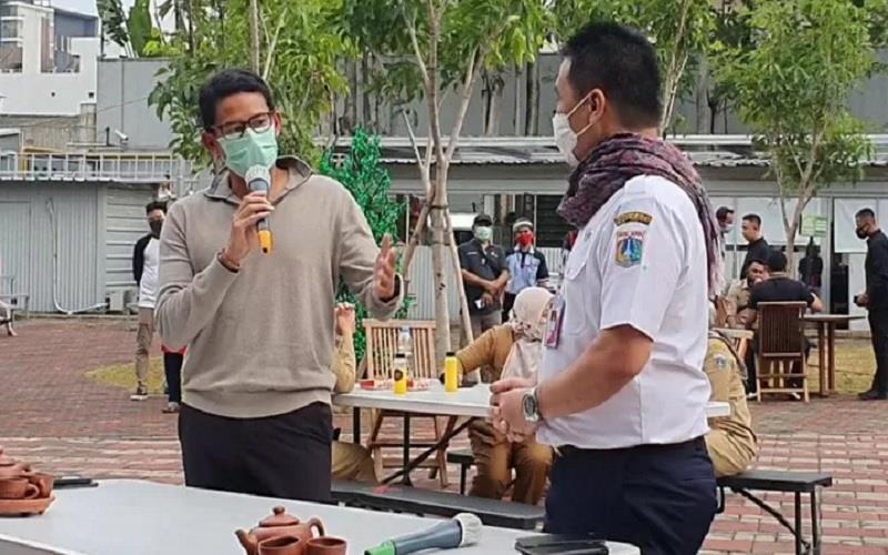 Menparekraf Sandiaga Uno menjelaskan asal- usul Kain Ulos yang dikalungkannya kepada Wagub DKI Jakarta Ahmad Riza Patria di Thamrin 10, Kamis (31/12/2020). - Antara\r\n