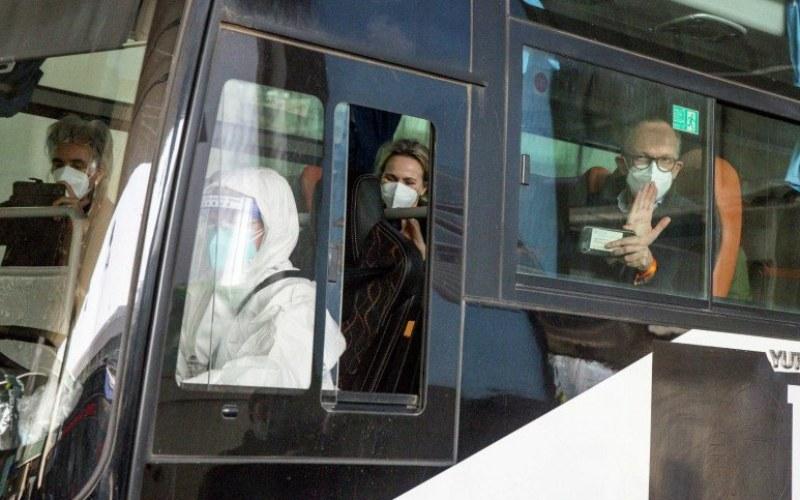 Anggota tim WHO yang bertugas menyelidiki asal-usul pandemi penyakit virus corona (Covid-19) duduk di bus yang meninggalkan Bandara Internasional Wuhan Tianhe di Wuhan, Provinsi Hubei, China, Kamis (14/1/2021)/Antara Foto - Reuters/Thomas Peter