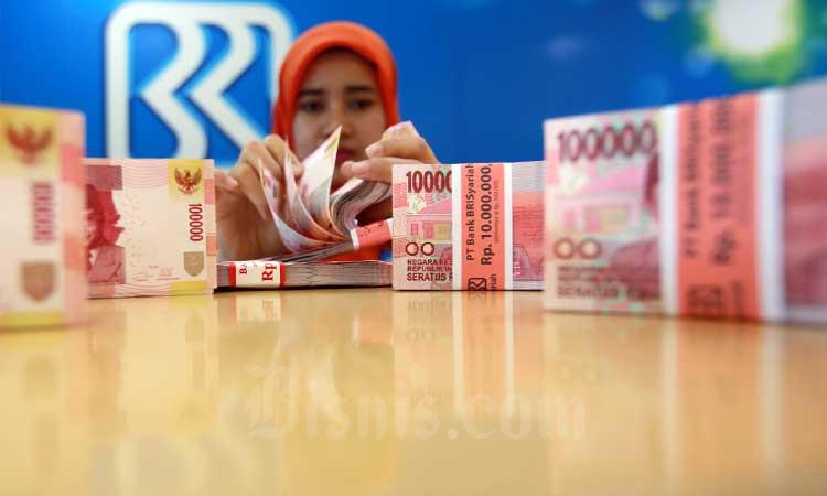 Karyawan menanta uang rupiah di kantor cabang Bank BRI syariah, Senin (3/7/2017). Bisnis - Abdullah Azzam