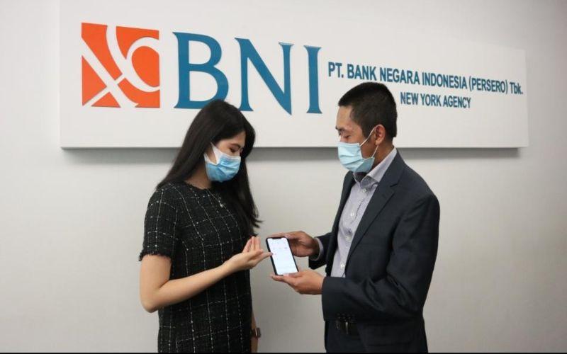 Pegawai sedang membantu nasabah untuk melakukan aktivasi BNI Mobile Banking di Kantor Cabang BNI New York.  - Dokumen BNI