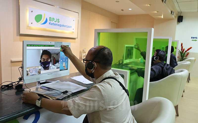 Peserta BP Jamsostek berkomunikasi dengan petugas pelayanan saat mengurus klaim melalui layar monitor dan tanpa kontak langsung di Kantor Cabang BP Jamsostek di Menara Jamsostek, Jakarta, Jumat (10/7/2020). Bisnis - Eusebio Chrysnamurti