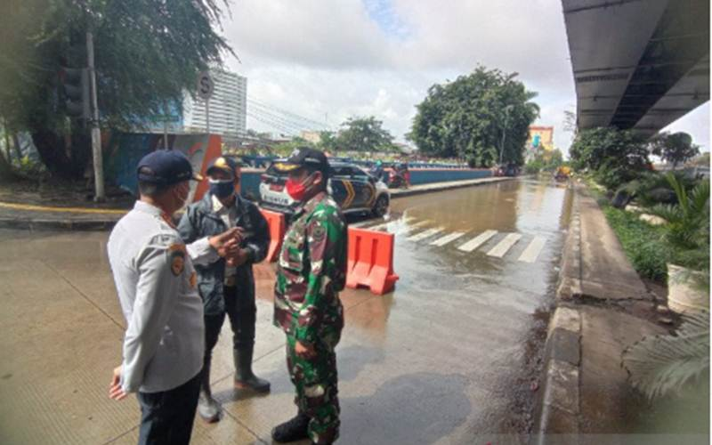 Petugas melakukan rekayasa lalu lintas akibat luapan Kali Ciliwung di kawasan Pademangan, Jakarta Utara, Senin (8/2/2021)./Antara/HO - Humas Pemkot Jakarta Utara