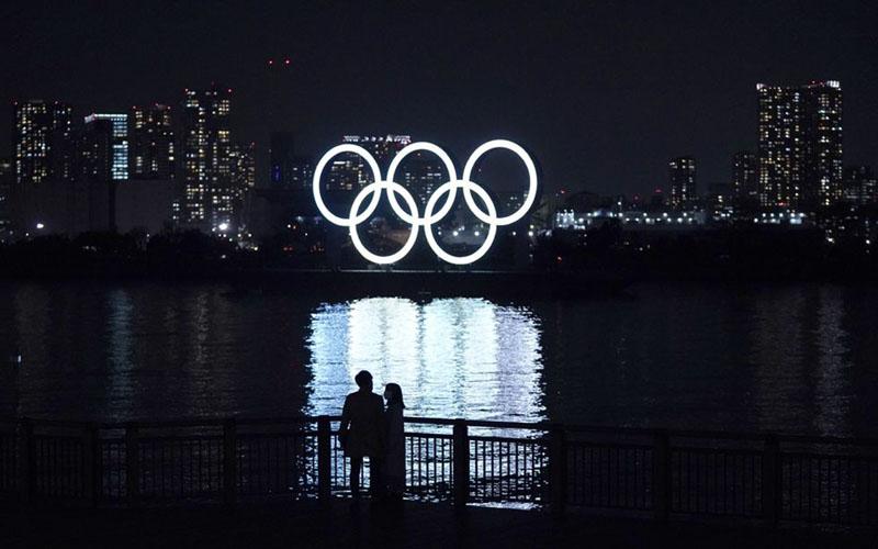 Cincin Olimpiade yang terang-benderang mengambang di perairan Odaiba, pulau buatan di Teluk Tokyo, Jepang./Bloomberg - Toru Hanai