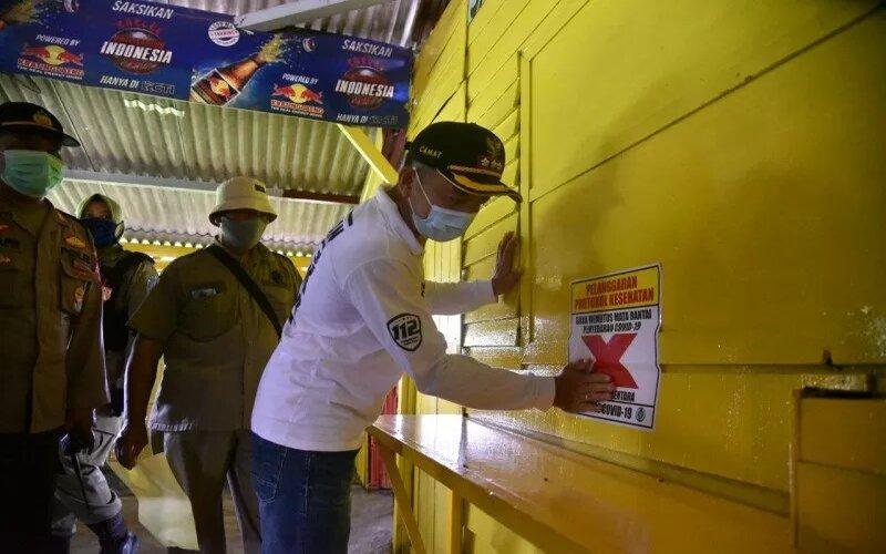 Camat Pakal Tranggono Wahyu Wibowo menempelkan tanda larangan berkegiatan di salah satu tempat hiburan di kawasan Jurang Kuping, Kelurahan Benowo, Kecamatan Pakal, Kota Surabaya, Jatim, Sabtu (13/2/2021). - Antara/Humas Pemkot Surabaya.