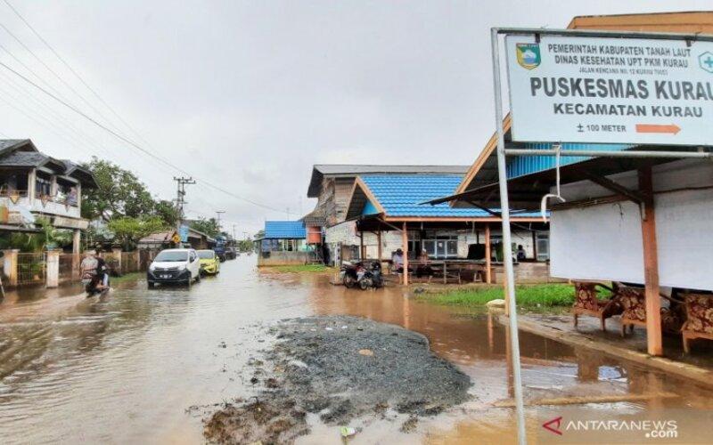 Jalan di Desa Kurau, Kabupaten Tanah Laut yang masih tergenang banjir di beberapa titik ketika pasang air laut dan terjadi hujan. - Antara/Firman