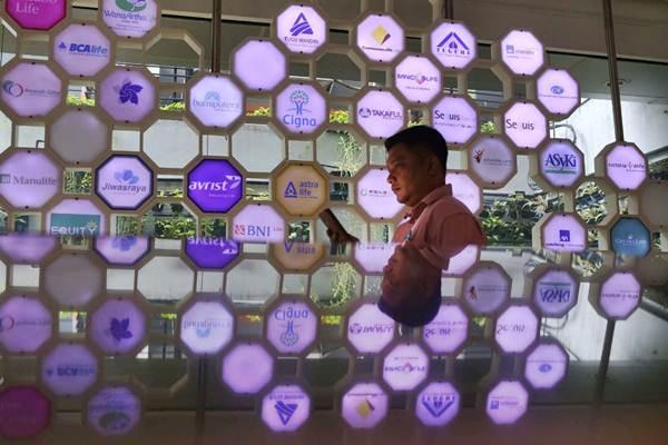 Karyawan berdiri di dekat logo perusahaan asuransi di kantor Asosiasi Asuransi Jiwa Indonesia (AAJI), di Jakarta, Selasa (15/1/2019). - Bisnis/Nurul Hidayat