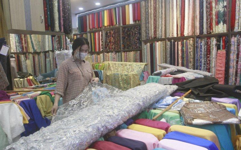 Pedagang merapikan kain di salah satu gerai di Pasar Tanah Abang, Jakarta, Selasa (8/12/2020).  - Bisnis.com/Himawan L Nugraha