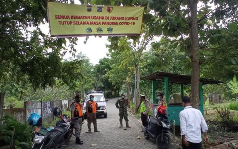 Sejumlah petugas keamanan berjaga di jalan akses menuju lokasi wisata Waduk Jurang Kuping, Kelurahan Benowo, Kecamatan Pakal, Kota Surabaya./Antara - Pemkot Surabaya