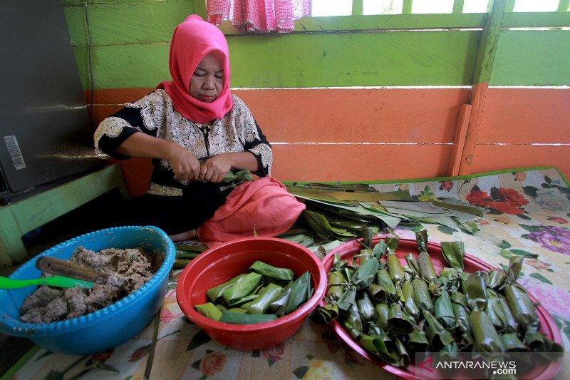 Seorang pedagang membungkus adonan makanan Ilabulo dengan daun pisang di Desa Butu, Kabupaten Bone Bolango, Gorontalo, Senin (2/9/2019)./ANTARA - Adiwinata Solihin