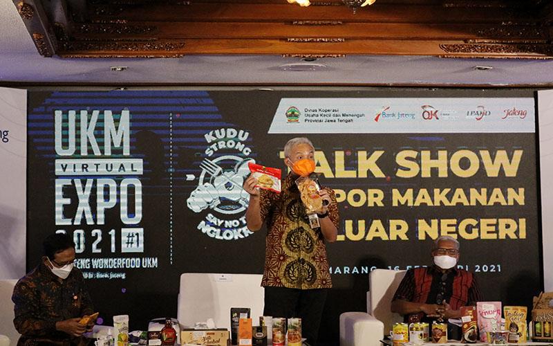 (Kiri ke Kanan) Kepala OJK Regional 3 Jawa Tengah dan DIY Aman Santosa, Gubernur Jawa Tengah Ganjar Pranowo, dan Direktur Utama Bank Jateng Supriyatno memamerkan produk UKM asal Jawa Tengah dalam acara UKM Virtual Expo 2021, Selasa (16/2/2021)  -  Muhammad Faisal Nur Ikhsan / BISNIS