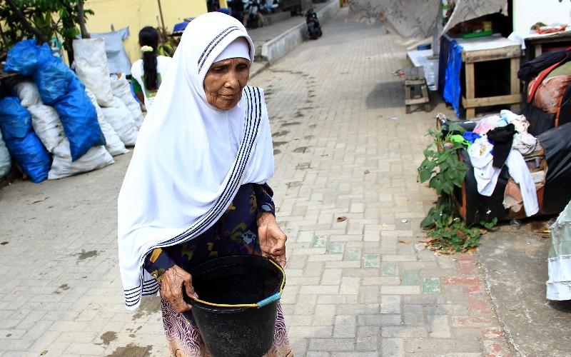 Seorang nenek di Batang Arau, Kecamatan Padang Selatan, Kota Padang, Sumatra Barat, tengah membawa air bersih menggunakan ember dan air itu diperoleh dari pendistribusian air bersih melalui mobil tangki BPBD Padang, Selasa (16/2/2021). Bisnis - Noli Hendra