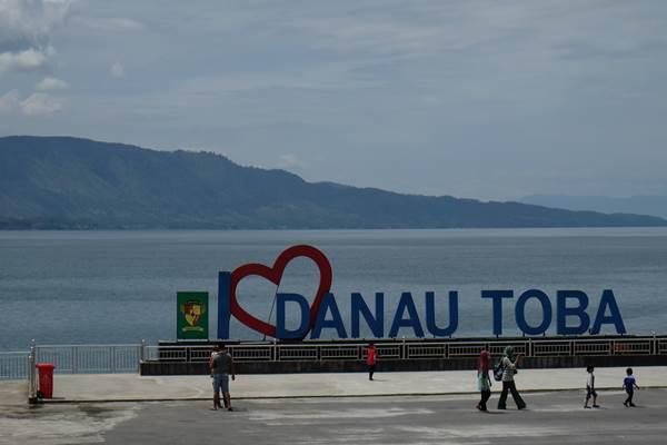 Wisatawan berada di Pantai Bebas Danau Toba, Parapat, Simalungun, Sumatra Utara./Antara - Irsan Mulyadi