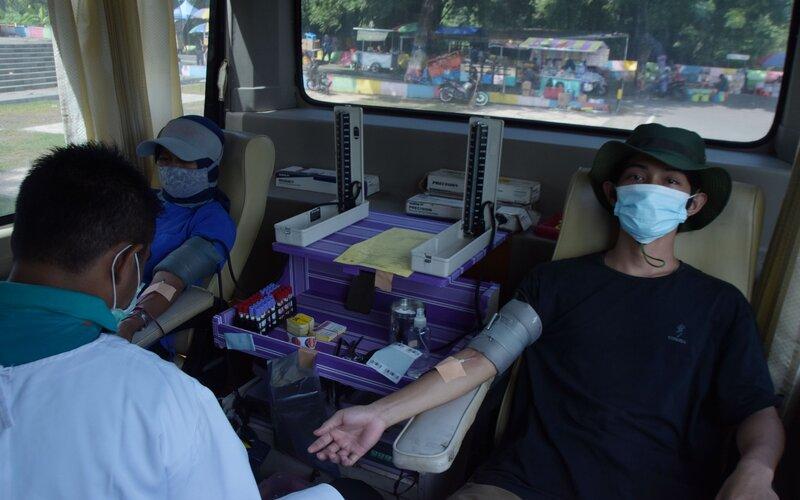 Petugas Palang Merah Indonesia (PMI) melakukan transfusi di dalam mobil Unit Donor Darah saat berada di kawasan Hari Bebas Kendaraan Bermotor atau Car Free Day (CFD) Kota Madiun, Jawa Timur, Minggu (7/2/2021). - Antara/Siswowidodo
