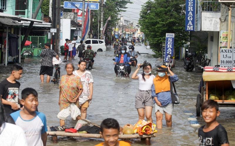 Sejumlah warga melintasi banjir yang merendam kawasan Sidokare, Sidoarjo, Jawa Timur, Selasa (16/2/2021). Sejumlah wilayah di Kabupaten Sidoarjo, Jawa Timur terendam banjir dengan ketinggian yang bervariasi menyusul tingginya intensitas hujan yang terjadi di wilayah setempat sejak Senin (15/2). - Antara/Umarul Faruq.