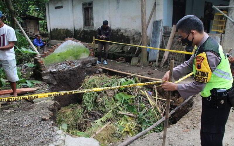 Polisi dibantu warga memasang garis polisi mengelilingi sumur yang ambles di Dukuh/Desa Jungkare, Kecamatan Karanganom, Rabu (17/2/2021). - Ist