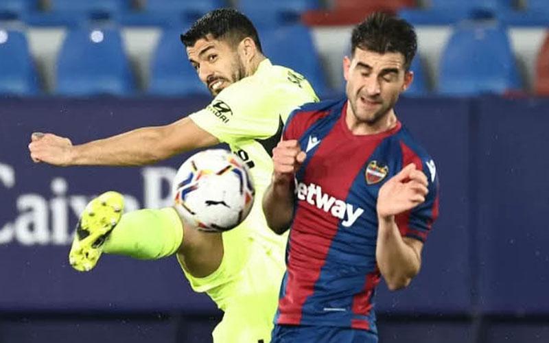 Striker Atletico Madrid Luis Suarez bertarung dengan bek Levante Sergio Postigo./Antara - AFP