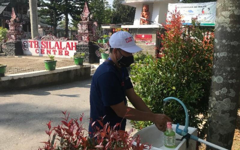 Salah seorang pengunjung mencuci tangan di depan pintu masuk Museum TB Silalahi Center, Kamis (18/2/2021). - Bisnis/Cristine Evifania Manik