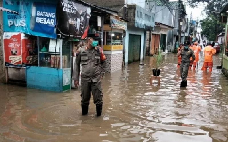 Petugas Satpol PP memantau genangan air yang terjadi di Jalan H Sulaiman, Cipinang Melayu, Kecamatan Makassar, Jakarta Timur, Selasa (16/2/2021). Genangan air terjadi akibat luapan saluran penghubung Sulaiman yang meluap. - Antara