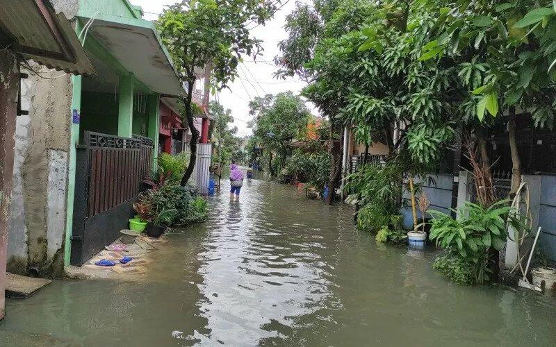 Warga melewati banjir di kawasan Perumahan Bukit Tiara, Cikupa, Kabupaten Tangerang, Sabtu (20/2/2021). - Antara/Indriani