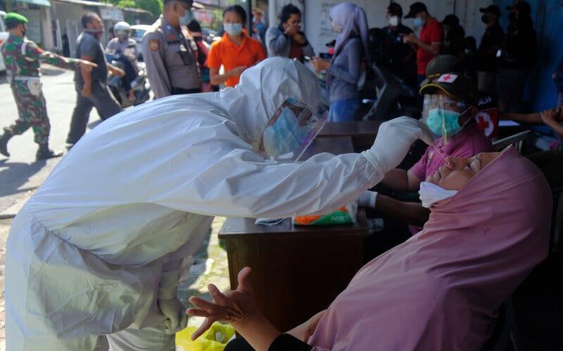 Petugas kesehatan mengambil sampel usap saat tes cepat antigen bagi pelanggar protokol kesehatan yang menjalani sanksi di Denpasar, Bali, Selasa (16/2/2021). - Antara/Nyoman Hendra Wibowo.