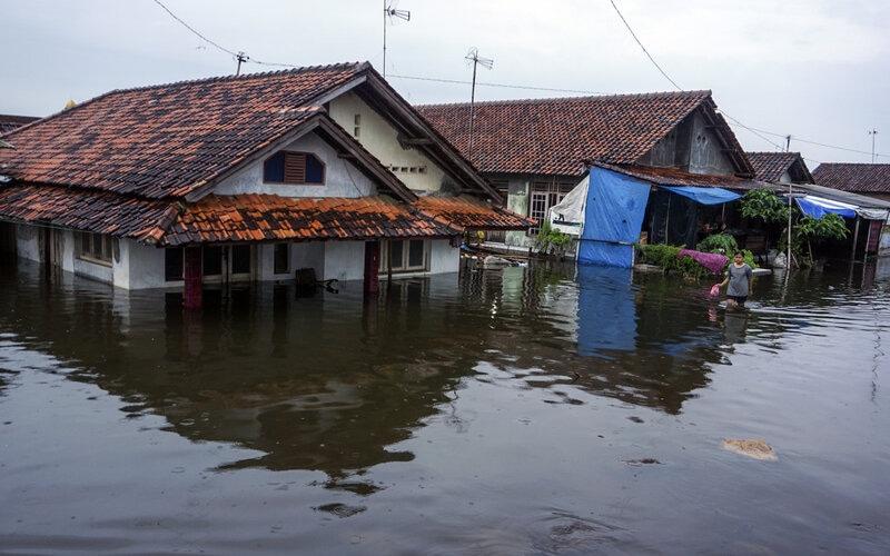 Warga berjalan di sekitar rumahnya yang tergenang banjir di Pekalongan, Jawa Tengah, Jumat (19/2/2021). Berdasarkan data Badan Penanggulangan Bencana (BPBD) Kota Pekalongan, banjir yang terjadi di Pekalongan sejak sekitar 14 hari yang lalu itu disebabkan oleh curah hujan yang tinggi dan mengakibatkan 17 kelurahan masih tergenang dan sebanyak 2.672 warga mengungsi. - Antara/Harviyan Perdana Putra.