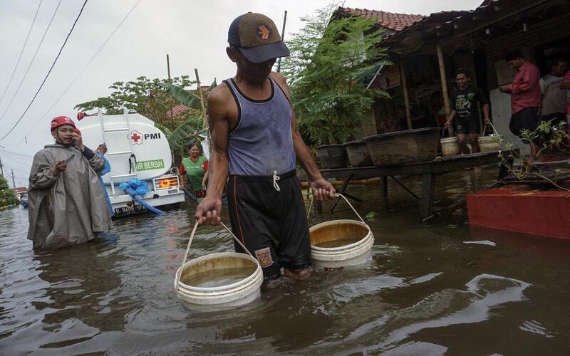 Warga membawa ember berisi air bersih dari Palang Merah Indonesia (PMI) di Pekalongan, Jawa Tengah, Jumat (19/2/2021). PMI Kota Pekalongan mendistribusikan air bersih sebanyak 1.500 liter per hari untuk warga terdampak banjir yang kekurangan air bersih. - Antara/Harviyan Perdana Putra.