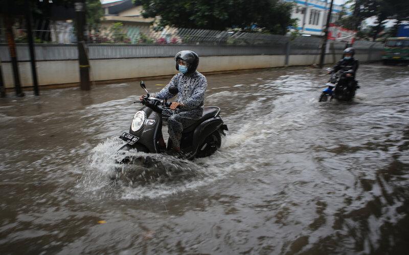 Pengendara motor melintas di jalan yang terendam banjir di kawasan Manis, Jatiuwung, Kota Tangerang, Banten, Kamis (18/2/2021). Hujan deras yang mengguyur kawasan tersebut sejak Kamis (18/2) pagi ditambah sistem drainase yang buruk menyebabkan banjir hingga ketinggian 70 cm./Antara- - Fauzan