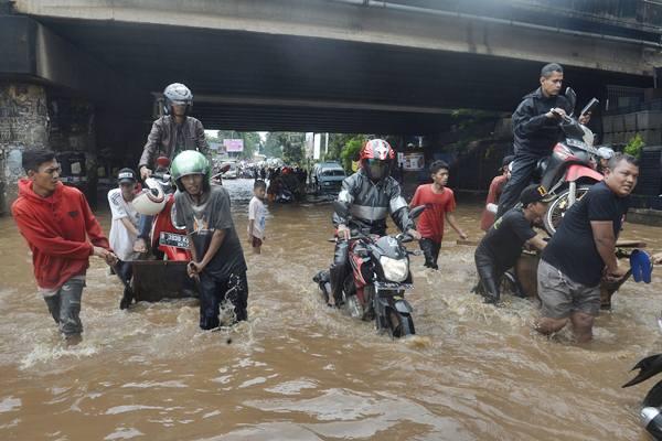 Pengendara motor menggunakan jasa angkut untuk melintasi banjir yang menggenangi bawah jembatan Tol JORR, Kali Malang, Bekasi, Jabar, Selasa (21/2). - Antara/Saptono